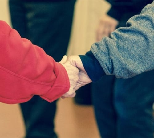 The cost of care - 2 people holding hands