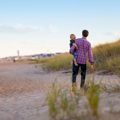 Inheritance Tax - man walking down the beach with his child