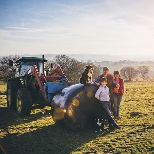 Family business - family standing around a tractor on their farm