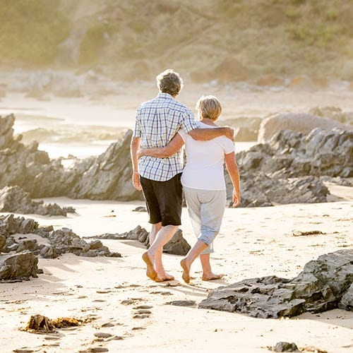 Wealth Management image - Elderly couple walking down the beach