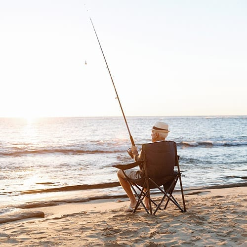 Corporate Pensions Image - Man Fishing By The Seaside On A Beach Chair