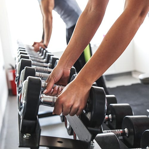 Employee Benefits image - Person picking up some dumbells at they gym