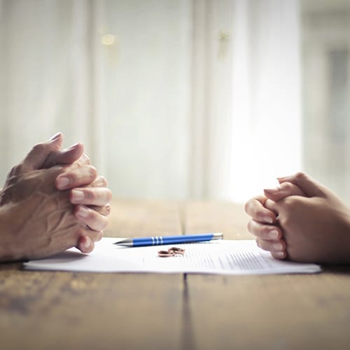 Couple Sitting At Table Over Divorce Papers