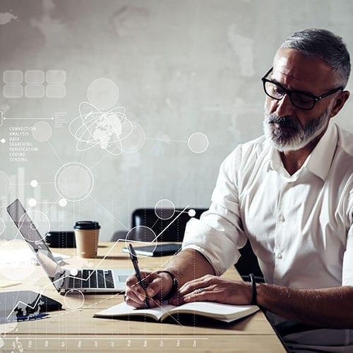 bearded man writing at desk