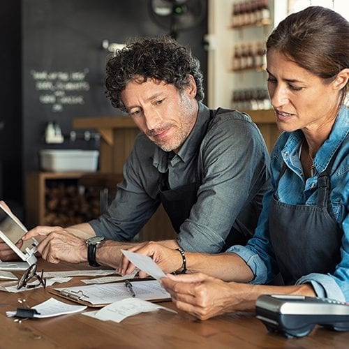 man and woman sitting in café discussing finance