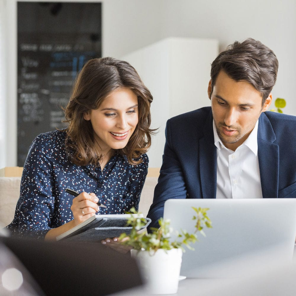 Man and woman sitting looking at laptop